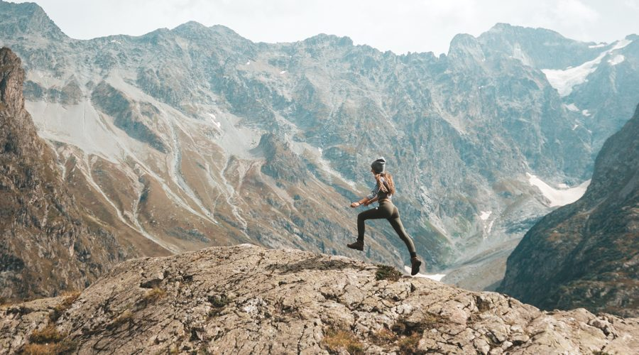 Woman running on mountain top.