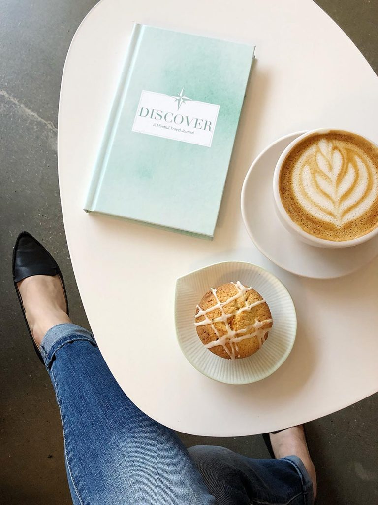 Latte, muffin and journal stacked on a table at Heirloom Brewshop in downtown Raleigh, NC