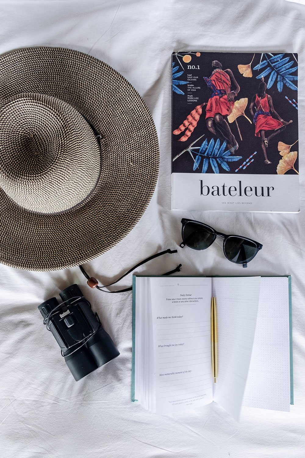 Journal on bed with binoculars, safari hat, and book