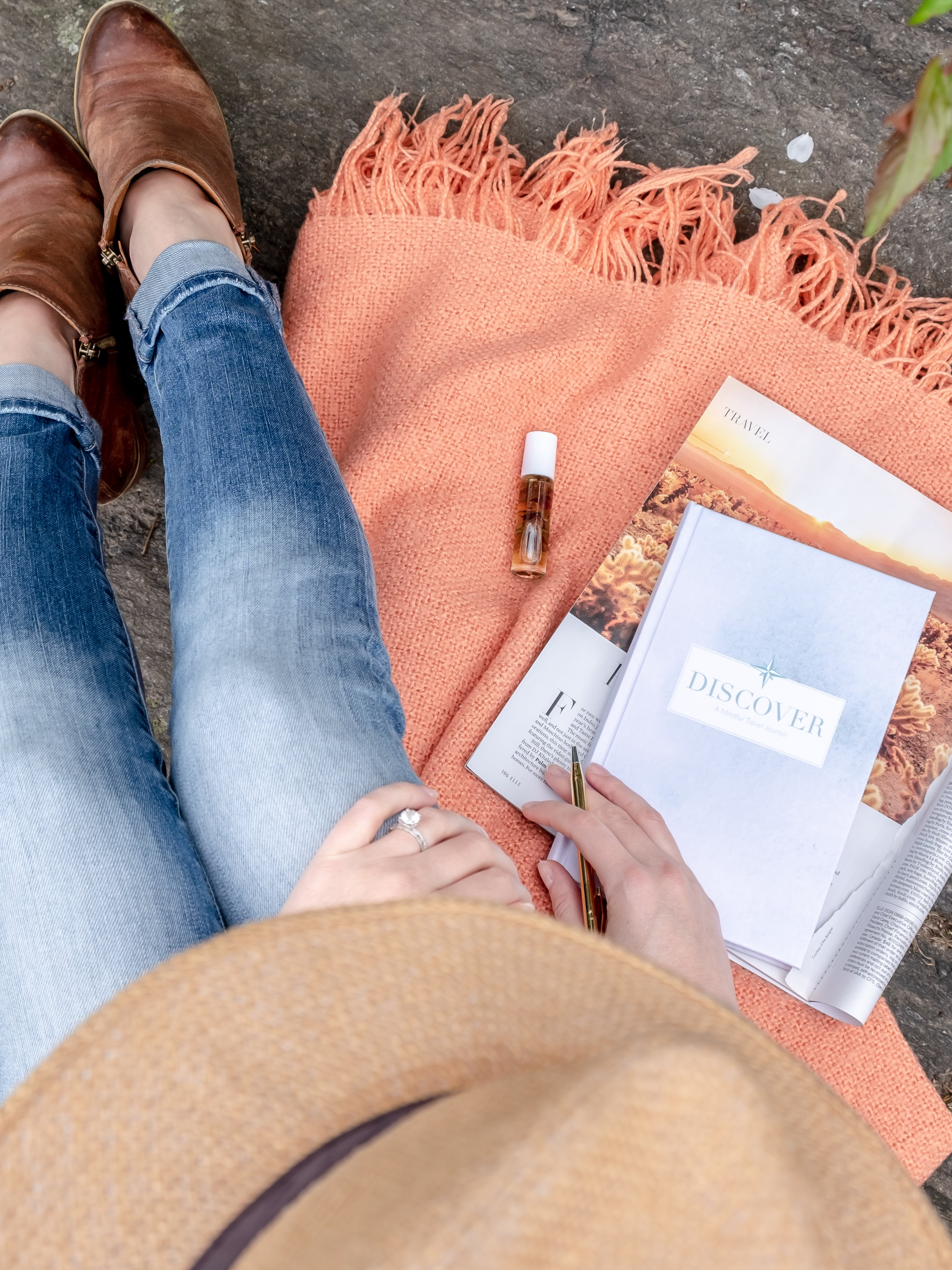 Woman using a travel journal with prompts in the park