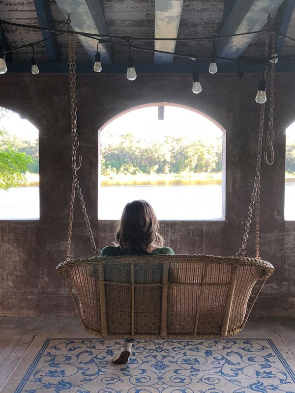 A woman overlooks a lake from a porch swing
